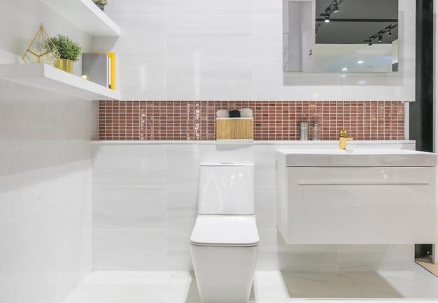 Salle de bain moderne et spacieuse avec des carreaux lumineux avec toilettes et lavabo.