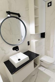 Salle de bain spacieuse et moderne avec carrelage en marbre avec une baignoire et un lavabo blancs impeccables vue latérale