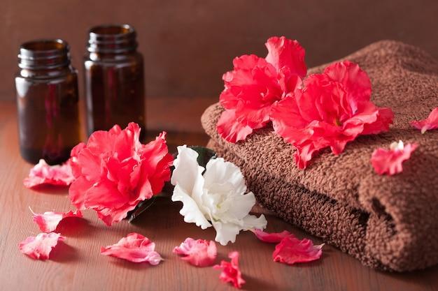 Salle de bains spa avec de l'huile essentielle de fleurs d'azalée sur fond rustique foncé