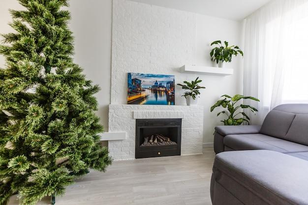 Salle blanche avec cheminée blanche. cheminée en pierre blanche arbre de noël au coin du feu
