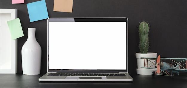 Salle de bureau à la mode avec ordinateur portable et fournitures de bureau sur tableau noir avec mur noir