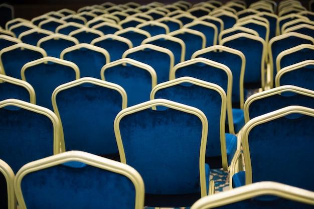 Salle de cinéma vide. un grand nombre de chaises en velours bleu dans une rangée.