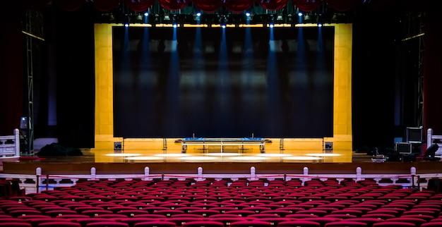 Salle de concert ou de spectacle. fauteuils sièges rouges et scène avant concert.