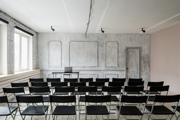 Salle de conférence avec beaucoup de chaises sombres. les murs sont blancs, intérieur loft. à droite, il y a une porte.