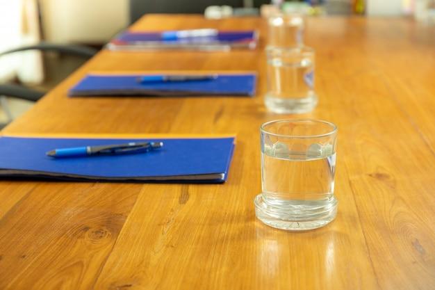 Salle de conférence vide avec de l'eau en verre et cahier avec un stylo sur la table en bois