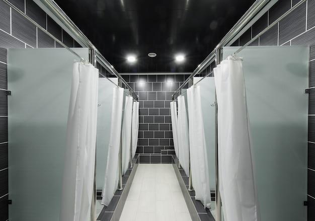 Salle de douche publique avec rideaux dans les cabines