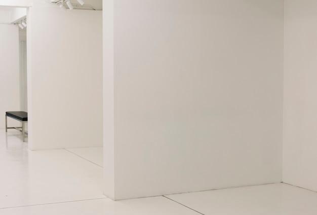 Salle d'exposition blanche avec un banc
