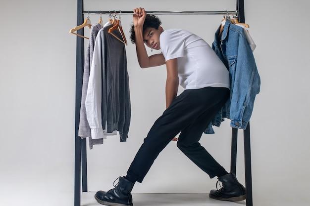 Salle d'exposition. jeune homme afro-américain tenant des cintres avec des vêtements et se penchant en avant