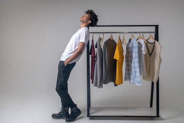 Salle d'exposition. jeune homme aux cheveux bouclés debout près des cintres avec des vêtements