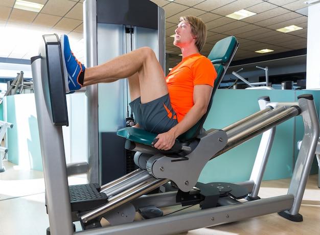 Salle de gym assis jambe presse machine homme blond séance d'entraînement