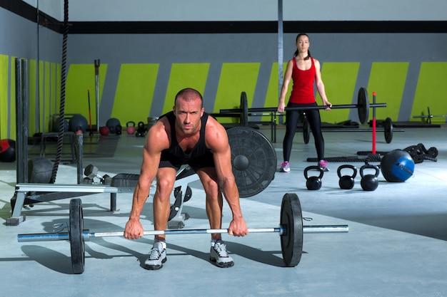 Salle de gym avec musculation barre d'entraînement homme et femme