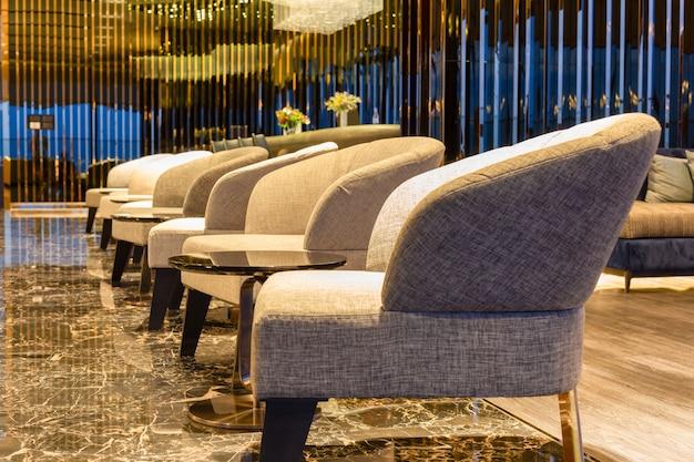 Salle intérieure avec rangée de fauteuils modernes sur sol en marbre.