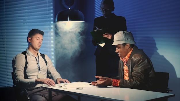 Salle d'interrogatoire enfumée avec un détective montrant des preuves de trafic de drogue à un suspect