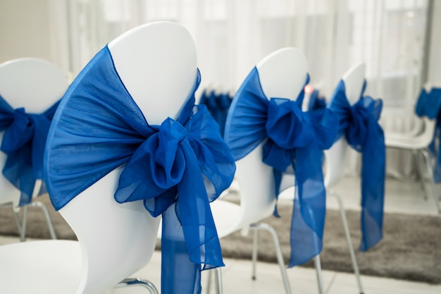 Salle lumineuse pour les mariages. rangées de chaises invités décorées de tissu bleu
