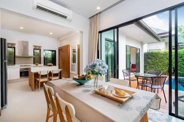 Salle à manger à aire ouverte avec vue sur la piscine à côté de la salle de séjour