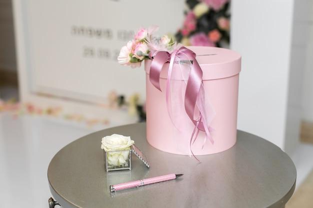 Salle de mariage. une table près de l'arc de mariage avec une tirelire pour des cadeaux aux nouveaux mariés