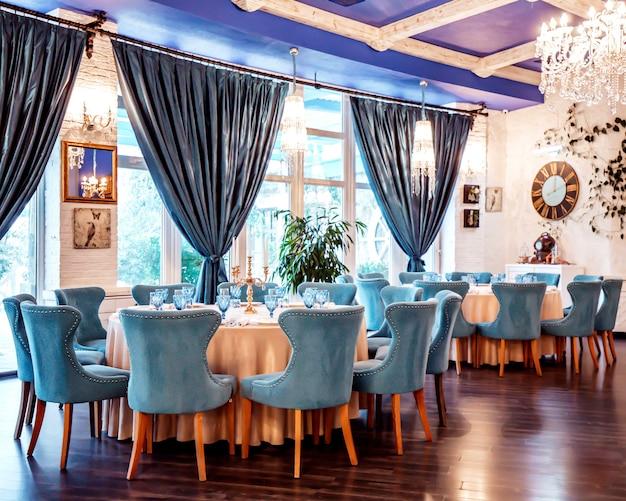 Salle de restaurant avec des chaises bleues et des décors sur le mur