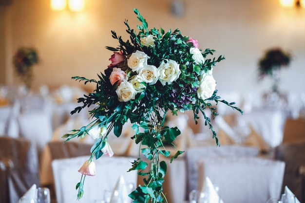 Salle de restaurant avec des tables décorées de grands vases avec des roses