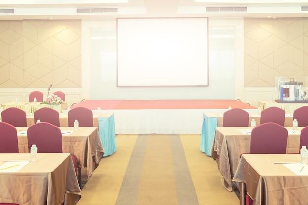 Salle de réunion de la conférence, rangée de chaises avec scène et écran vide pour réunion d'affaires, conférence