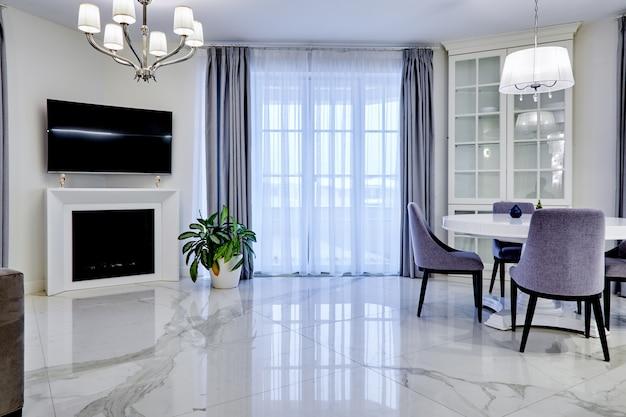 Salle de séjour intérieure minimaliste dans les tons clairs avec sol en marbre, grandes fenêtres et une table pour quatre personnes