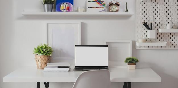 Salle de travail à la maison minimale avec un ordinateur portable à écran blanc avec décorations