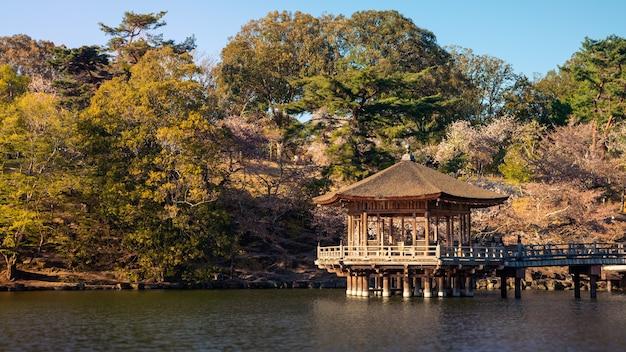Salle ukimi-do au-dessus de l'étang dans le parc de nara pendant les fleurs de sakura, japon. temple hexagonal flottant dans le lac sagi-ike