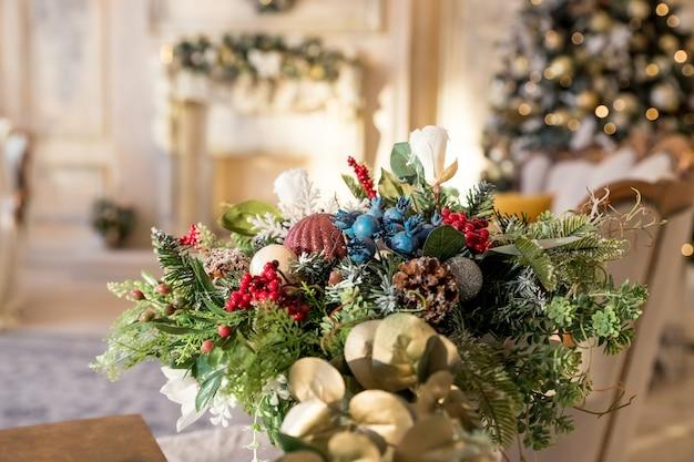 Salon arbre de noël, cheminée contemporaine, appartement design intérieur loft. composition de table, vase en sapin avec neige artificielle, boules, arcs, perles contre l'intérieur festif