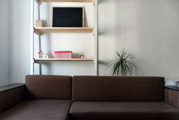 Salon aux couleurs claires. canapé marron et étagère en bois. intérieur