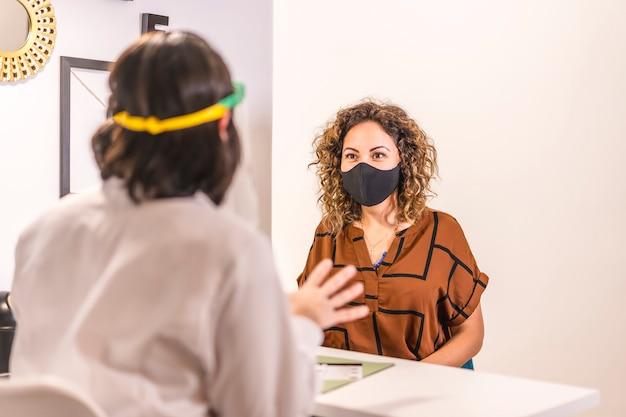 Salon de beauté, réouverture après la pandémie de coronavirus avec des mesures de sécurité. un client avec un masque facial dans le salon de beauté est attentif aux explications. covid-19