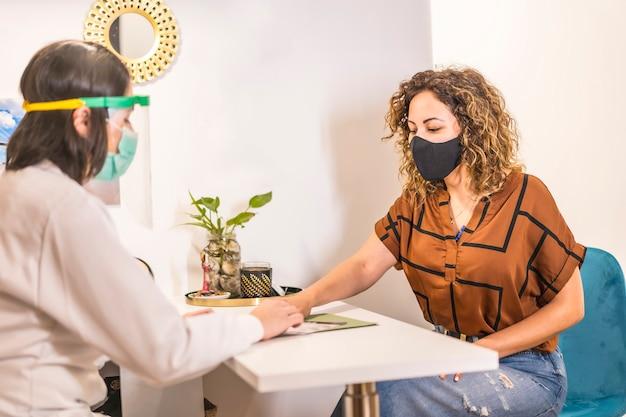 Salon de beauté, réouverture après la pandémie de coronavirus avec des mesures de sécurité. un client avec un masque facial dans le salon de beauté a parlé au médecin. covid-19