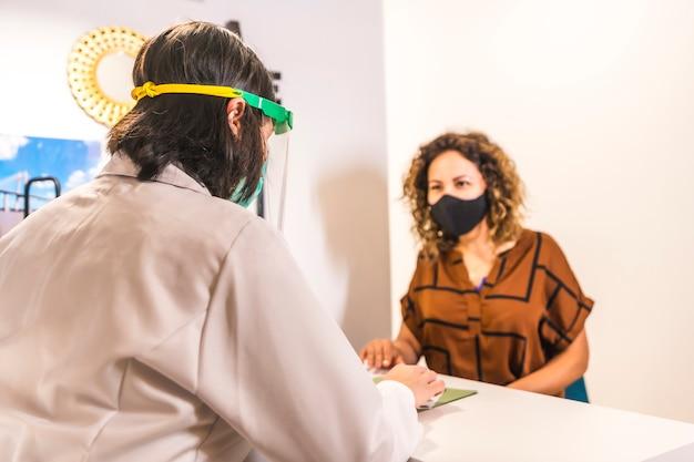 Salon de beauté, réouverture après la pandémie de coronavirus avec des mesures de sécurité. femme médecin s'occupant d'un patient dans le salon de beauté. covid-19