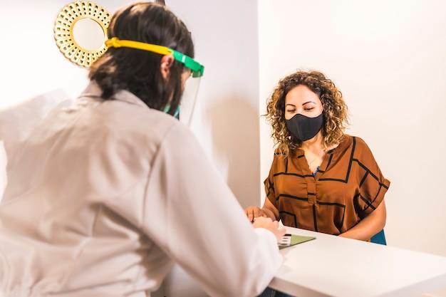 Salon de beauté, réouverture après la pandémie de coronavirus avec des mesures de sécurité. femme médecin s'occupant d'un patient dans le salon de beauté avec des mesures de sécurité. covid-19