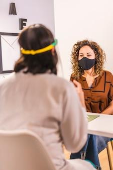 Salon de beauté, réouverture après la pandémie de coronavirus avec des mesures de sécurité. offrir un budget au client avec un masque facial. covid-19