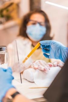 Salon de beauté, réouverture de l'entreprise après la pandémie de coronavirus. un client avec un masque facial recevant un traitement sur ses mains. covid-19