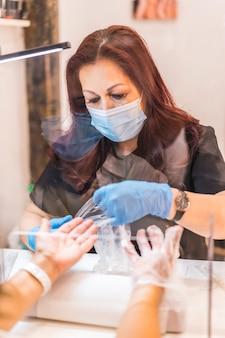 Salon de beauté, réouverture de l'entreprise après la pandémie de coronavirus. un client soutenant ses mains avec une crème dans un traitement très spécial. covid-19