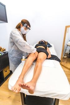 Salon de beauté, réouverture de l'entreprise après la pandémie de coronavirus. un employé avec des protections effectuant un massage sur les jambes. covid-19