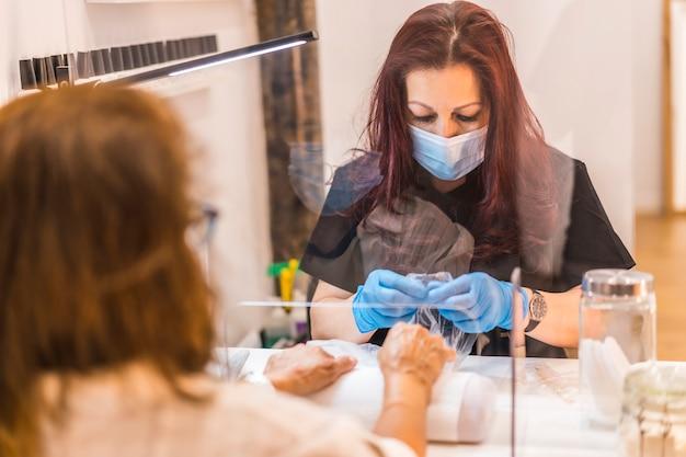 Salon de beauté, réouverture de l'entreprise après la pandémie de coronavirus. manucure et pédicure spéciales avec mesures de sécurité pour un travailleur latina. covid-19