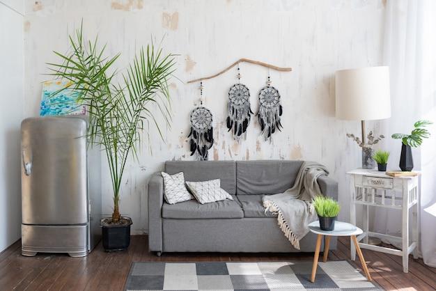 Salon avec canapé gris et capteur de rêves