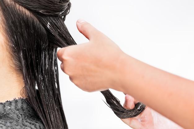 Salon de coiffure appliquant un traitement capillaire. appliquer une couleur crème sur les cheveux.