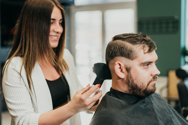 Salon de coiffure belle fille coupe un homme barbu dans le salon