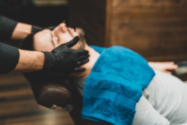 Salon de coiffure. le client dans la chaise du maître dans le salon de coiffure, le barbier applique de l'huile et des cosmétiques sur la barbe du client. boutique de beauté masculine. mode de vie sain et beauté.