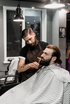 Salon de coiffure coupe la barbe du client dans le salon de coiffure