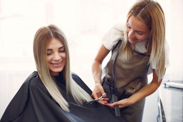 Salon de coiffure coupe les cheveux de son client dans un salon de coiffure