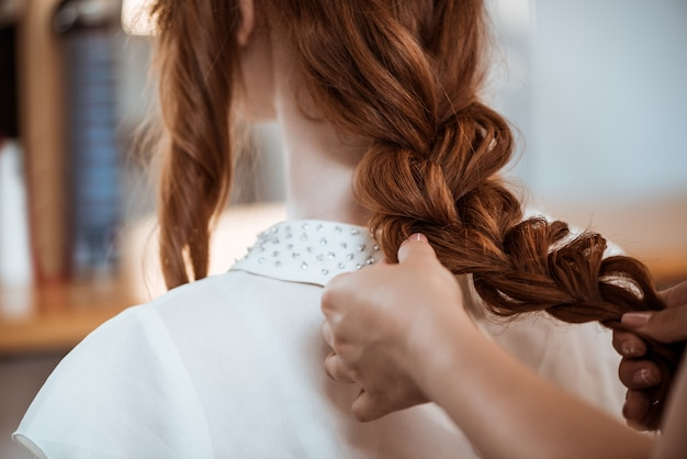 Salon de coiffure féminine faisant coiffure à femme rousse dans un salon de beauté