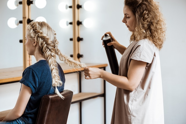 Salon de coiffure féminine faisant coiffure pour femme blonde dans un salon de beauté
