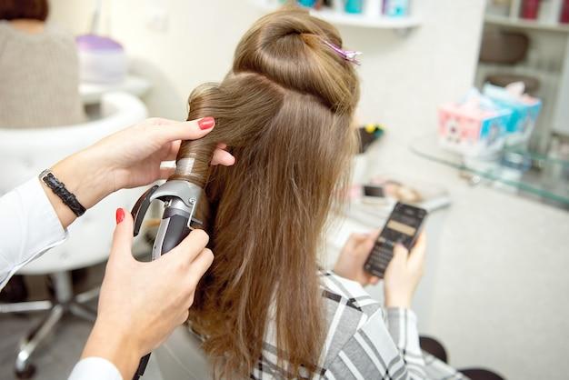 Salon de coiffure femme faisant coiffure pour fille blonde dans un salon de beauté.