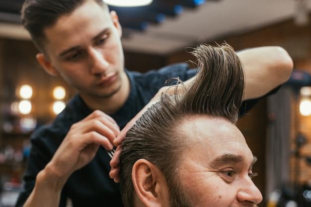 Salon de coiffure, un homme avec une barbe coupe coiffeur.