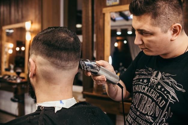 Salon de coiffure, un homme avec un coiffeur coupe barbe.