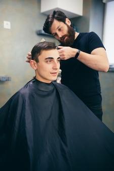 Salon de coiffure. l'homme coupe les cheveux d'un autre homme. fait une coiffure