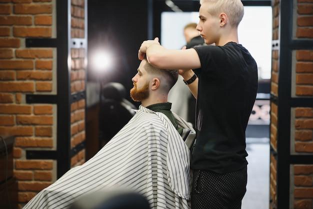 Salon de coiffure. homme dans une chaise de coiffeur, coiffeur coiffant ses cheveux